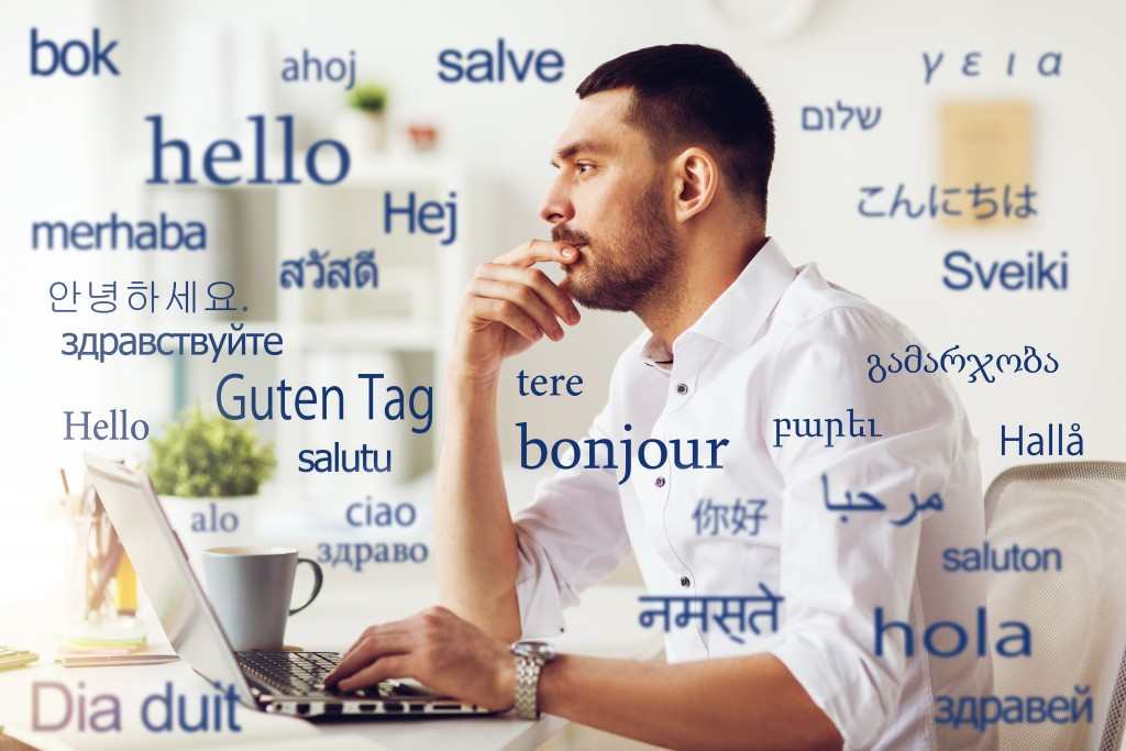 translation, business, and technology concept - male translator or businessman with laptop computer thinking at office over greeting words in different foreign languages