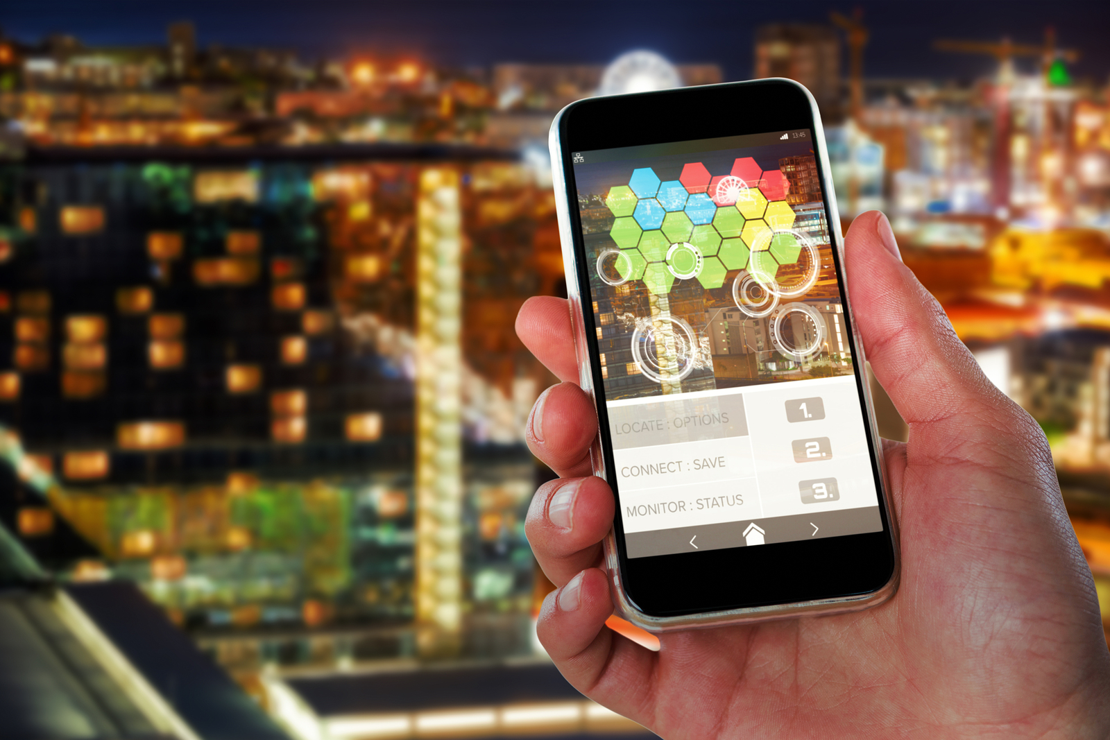 Close-up of hand holding 3D mobile against illuminated beautiful buildings in city
